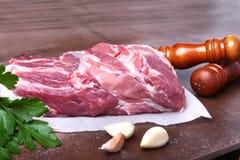 Surowy wieprzowiny szyi kotlecika mięso z pietruszki ziele opuszcza na kamiennym tle, ostrzarz dla pikantność i czosnek Przygotow Zdjęcia Stock
