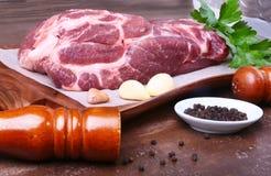Surowy wieprzowiny szyi kotlecika mięso z pietruszki ziele opuszcza na kamiennym tle, ostrzarz dla pikantność i czosnek Przygotow Zdjęcie Royalty Free
