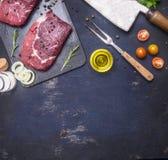 Surowy wołowina stek z rozmarynami, masłem i mięsnym rozwidleniem na ciemnej nieociosanej tnącej desce, odgórny widok z przestrze Zdjęcie Royalty Free