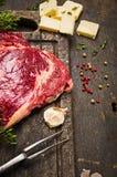 Surowy wołowiny mięso z składnikami dla gotować na nieociosanym drewnianym tle Zdjęcie Stock