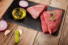 Surowy wołowina stek na ciemnej desce Fotografia Royalty Free