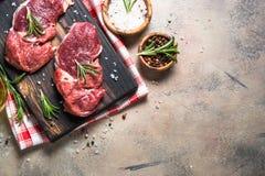 Surowy wołowina stek z ziele na kamienia stole Odgórny widok Obraz Stock