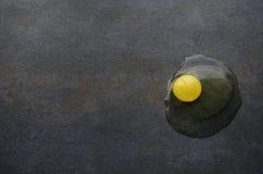 Surowy yolk na zmroku stole w kuchni rozbite jajko zdjęcia stock