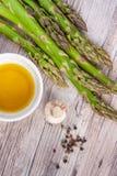 Surowy zielony asparagus wywodzi si? na drewnianej powierzchni, mieszkanie nieatutowy zdjęcie stock