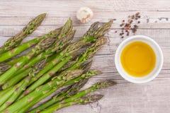 Surowy zielony asparagus wywodzi si? na drewnianej powierzchni, mieszkanie nieatutowy fotografia stock