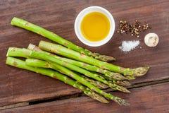 Surowy zielony asparagus wywodzi si? na drewnianej powierzchni, mieszkanie nieatutowy zdjęcia stock
