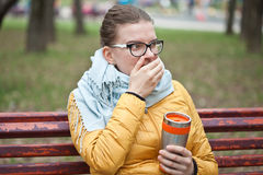 Surpeisings jonge vrouw met hete drank in het park Royalty-vrije Stock Afbeeldingen