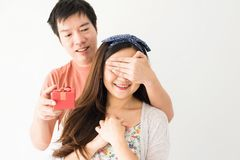 Surpirse gift to cute girlfriend. Handsome Asian boyfriend hands close his girlfriend eyes and giving surprise gift while Happy exciting girl laugh with copy Royalty Free Stock Photo