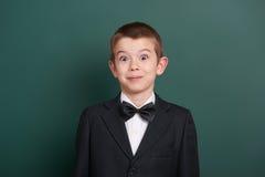 Surpised在绿色空白的黑板背景附近的男生画象,穿戴在经典黑衣服,一个学生,教育概念 免版税库存图片
