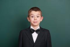 Surpised在绿色空白的黑板背景附近的男生画象,穿戴在经典黑衣服,一个学生,教育概念 库存照片
