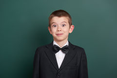 Surpised school boy portrait near green blank chalkboard background, dressed in classic black suit, one pupil, education concept Royalty Free Stock Images