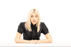 Surpised young woman sitting on a table Stock Photo