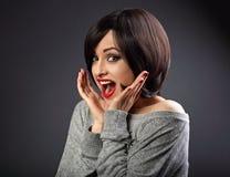 Surpreendente excite muito a mulher que olha com a boca aberta no gre escuro fotografia de stock