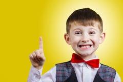 Surpreendido apontando o rapaz pequeno isolado sobre o fundo amarelo Fotografia de Stock