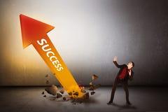 Surpresa asiática do homem de negócio que olha a seta do sucesso para fora da parte inferior Fotos de Stock Royalty Free