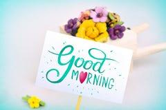 Surpresa da manhã, carrinho de mão com flores e um cartão Uma inscrição colorida é um bom dia fotografia de stock