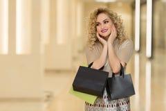 A surpresa da mulher guarda mordentes à mão Menina bonita com sacos de compras que aponta à vista à esquerda Apresentando seu pro imagem de stock
