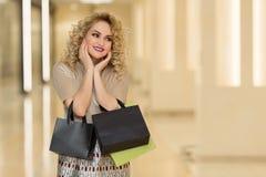 A surpresa da mulher guarda mordentes à mão Menina bonita com sacos de compras que aponta à vista direito Apresentando seu produt Imagem de Stock