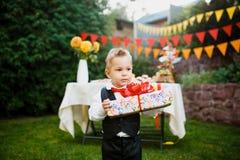 Surpresa para o aniversário o menino está guardando uma caixa com um presente na jarda no fundo de uma tabela festiva com um bolo foto de stock