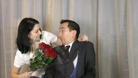 Surpresa ruim A mulher que preparam a surpresa a um homem que senta-se no sofá e o homem obtêm assustado filme