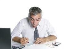 Surpresa sênior da verificação de banco do sinal do homem de negócios Fotos de Stock Royalty Free