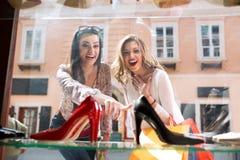 2 surpriced девушка показывая на элегантных ботинках Стоковая Фотография