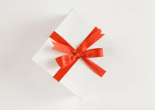 Surprise. The beautiful white box with a red bow lies on a white background Royalty Free Stock Photo