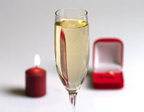 Surprise. Champagne glass, candle and box with a gift Stock Image