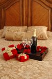 Surprise. Presents, champagne, roses on a bed Royalty Free Stock Photo