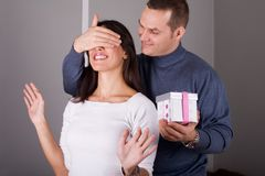 Surprise. Young couple at home celebrating holiday or engagement Stock Image