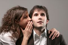 Surprise. One woman telling secret to man - close up, portrait Royalty Free Stock Images
