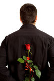 Surprise. Young man holding a rose behind his back as a surprise for a girl Stock Photo