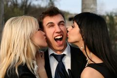 Surprise. Two girl kissing man outdoors Stock Photos