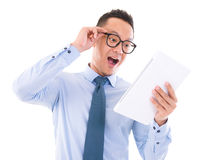 Surprise Asian business man looking at tablet. Computer, isolated over white background Stock Image