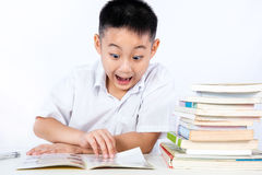 Surprise Asian Chinese Little Boy Wearing Student Uniform Readin. G Textbook in plain isolated white background Stock Photos