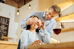 Inspired man closing his womans eyes. Surprise. Attractive exuberant blond men closing his womans eyes and smiling while drinking wine in a cafe Royalty Free Stock Photography