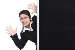 Surprise from behind blackboard. A woman is trying to give surprise appeared from behind the blackboard. You can place text, announcement or advertisement on the Royalty Free Stock Image
