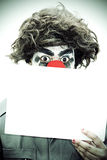 Surprise Birthday Clown Holding Sign. Surprise Birthday Clown Peers Over A Blank Sign With A Look Of Wide Eye Shock In A Party Invitation Concept Royalty Free Stock Images
