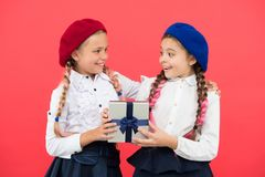 Surprise for both. Girl giving gift box to friend. Girls friends celebrate holiday. Children with wrapped gift. Open stock photos