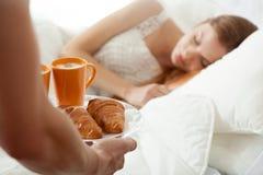 Surprise breakfast for sleeping woman. Surprise breakfast for sleeping women in bed Stock Photo