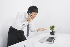 Surprise businessman using cell phone and laptop in office Stock Image