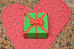 Surprise cake covered with fondant. Closeup of a present shaped surprise cake on a love heart, decorated with fondant stock photography