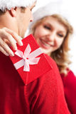 Surprise christmas gift. A portrait of a happy cute caucasian girl receiving a surprise christmas gift from his boyfriend (focus on the gift box Royalty Free Stock Image