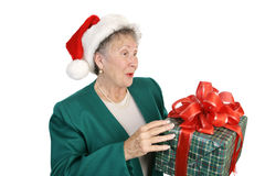 Surprise Christmas Package. A pretty senior lady holding a surprise Christmas gift.  Isoalted on white Stock Image