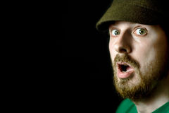 Surprise concept - amazed young man. Portrait of shocked bearded man on black background Stock Photo