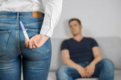 Surprise darling!. Woman is hiding pregnancy test behind her back Royalty Free Stock Images