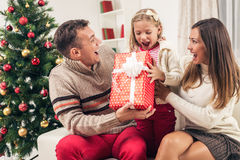 Surprise For Daugter. Cheerful Parent surprise their cute little girl with Present for Christmas or New Year Stock Photography