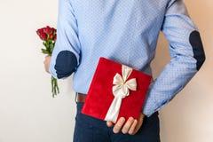 Surprise de cadeau de jour de valentines, cadeau de dissimulation d'homme et tenir le bouquet rose rouge image libre de droits