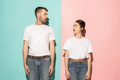 Wow. Doubtful pensive couple with thoughtful expression making choice against pink background. Surprise. Doubt concept. Doubtful pensive couple with thoughtful stock image