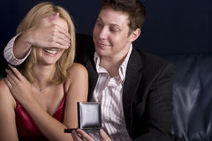 Surprise gift. Man surprising his girlfriend with a present on valentines day Royalty Free Stock Photos